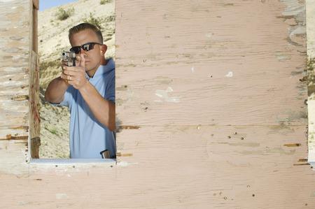 Man aiming hand gun at firing range Stock Photo - 3811750