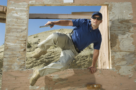 Man with hand gun jumping obstacle at firing range Stock Photo - 3811767