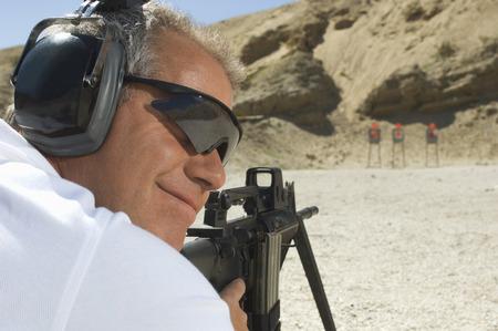 aims: Man aiming machine gun at firing range