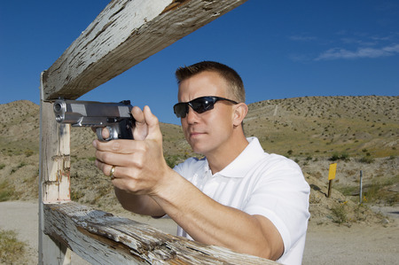 combat sport: Man aiming hand gun at firing range