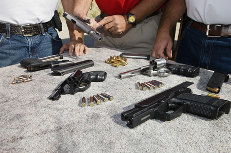man holding gun: Three men with table of guns, mid section, close-up LANG_EVOIMAGES