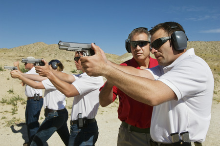 Instructor assisting men aiming hand guns at firing range