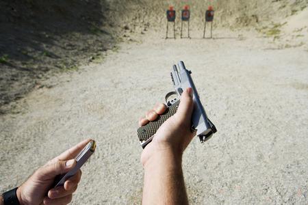 adult magazines: Man loading hand gun at firing range, focus on hands LANG_EVOIMAGES