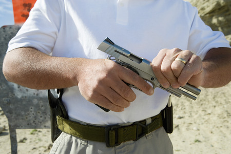 Man loading hand gun at firing range, mid section Stock Photo - 3811707