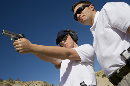 Instructor assisting woman aiming hand gun at firing range, low angle view Stock Photo