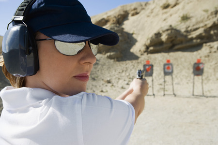 Woan aiming hand gun at firing range Stock Photo