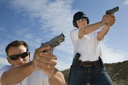 target shooting: Man and woman aiming hand guns at firing range