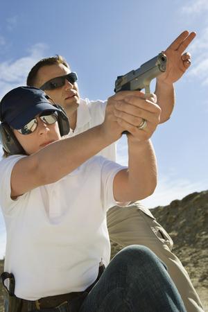 target shooting: Instructor assisting woman aiming hand gun at firing range