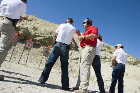 Instructor assisting people aiming guns at firing range Stock Photo - 3811796