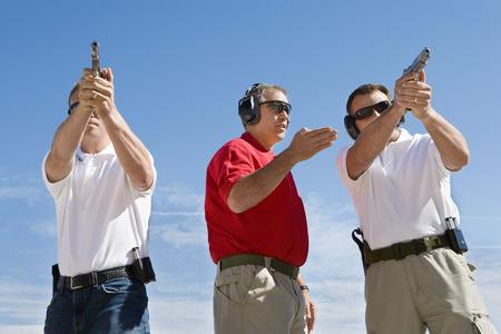 Instructor assisting men aiming hand guns at firing range Stock Photo - 3811732