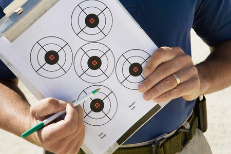Instructor holding clipboard with target diagram, mid section Stock Photo - 3811749