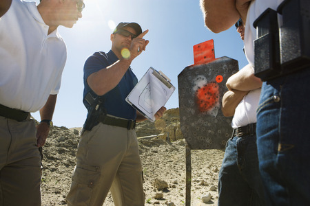 Instructor holding clipboard with target diagram at combat training Stock Photo - 3811751