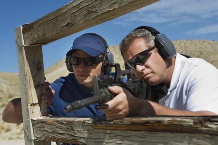 gun man: Instructor with man aiming machine gun at firing range LANG_EVOIMAGES