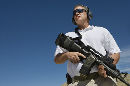Man holding machine gun at firing range, low angle view Stock Photo - 3811613
