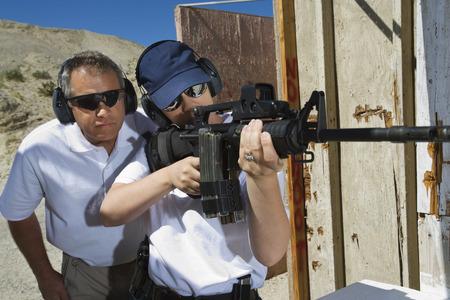 informant: Instructor assisting woman aiming machine gun at firing range