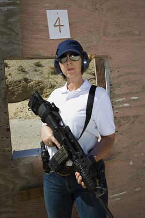 Woman holding machine gun at firing range, portrait Stock Photo - 3811748