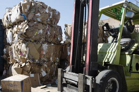 camion de basura: Las pilas de cajas de cart�n reciclado en el centro y carretilla elevadora
