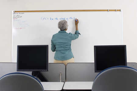 writing activity: Female teacher writing on whiteboard in computer classroom