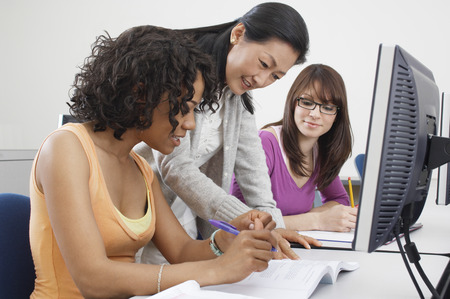 tuition: Two female students working with teacher in computer classroom