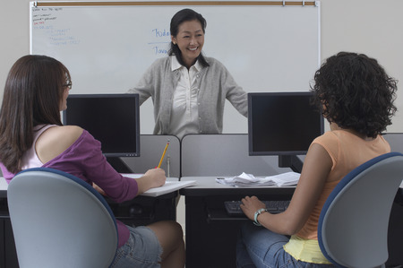 teaching material: Two female students working with teacher in computer classroom