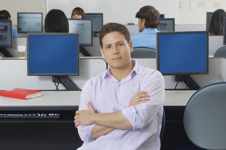 one person with others: Male student sitting in computer classroom, portrait LANG_EVOIMAGES
