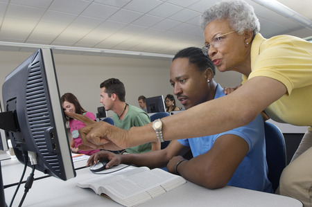 Teacher helping student in computer class Stock Photo