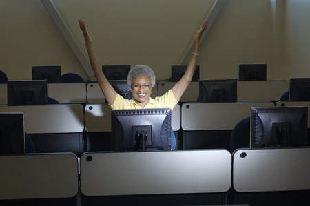 Mature female student celebrating in computer classroom Stock Photo - 3812078