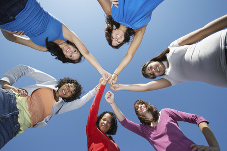 huddle: Young women standing in circle, view from below LANG_EVOIMAGES
