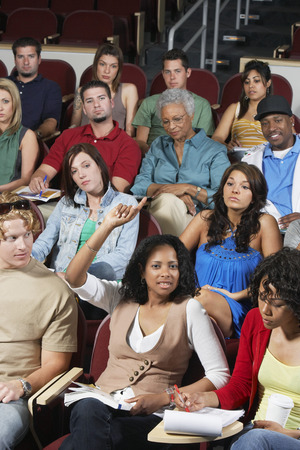 writing activity: Group of people in classroom, one woman with raised arm