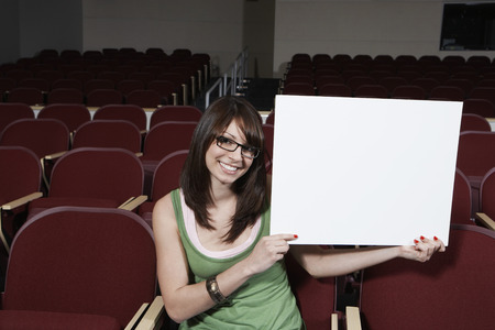 Female student holding blank board in lecture theatre, portrait Stock Photo - 3811872
