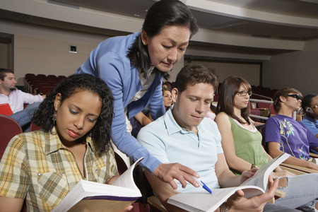 Female teacher assisting students during lesson Stock Photo - 3812105