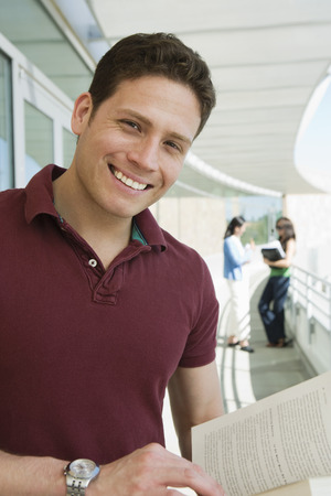 further education: Male student holding book at school, smiling, portrait