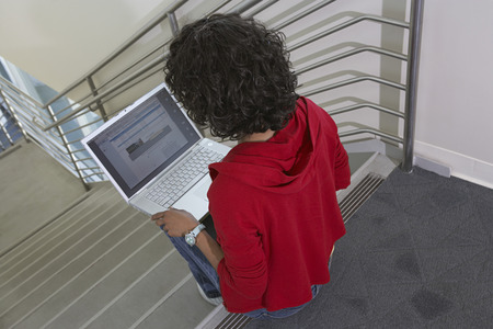lap top: Female student using laptop on stairs LANG_EVOIMAGES