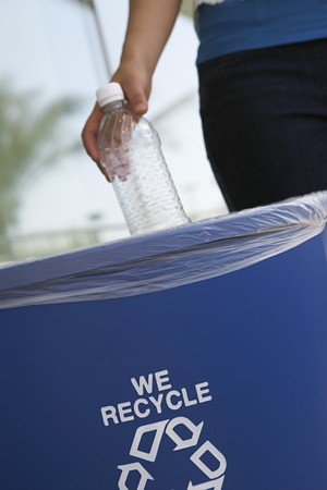 recycling logo: Person recycling plastic bottle, close-up