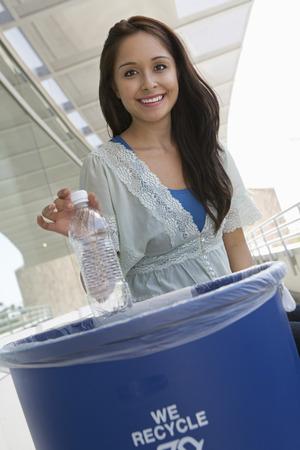 kunststof fles: Jonge vrouw recycling plastic fles, portret LANG_EVOIMAGES