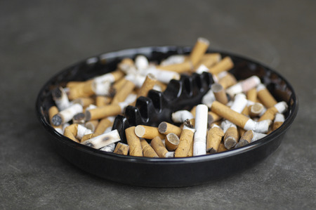 Full ashtray of cigarettes on table, close-up Stock Photo - 3812035