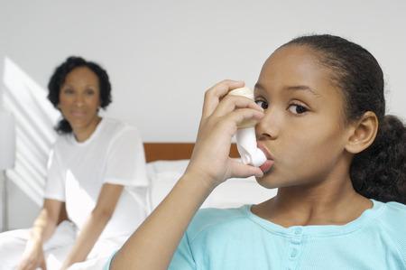 inhaler: Nurse watching girl (7-9) using inhaler in hospital