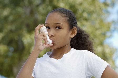 hair blacks: Girl (7-9) using inhaler, outdoors
