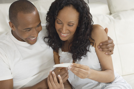 Couple examining pregnancy test in bed Stock Photo - 3813051
