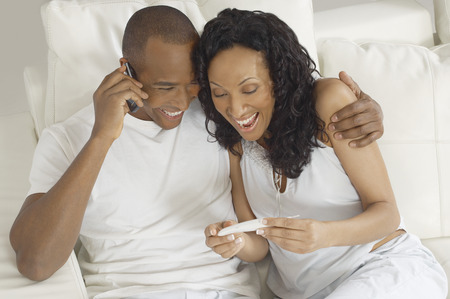 Couple examining pregnancy test in bed, man using mobile phone Reklamní fotografie - 3813011