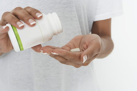 Woman holding bottle of pills, mid section Stock Photo - 3812756