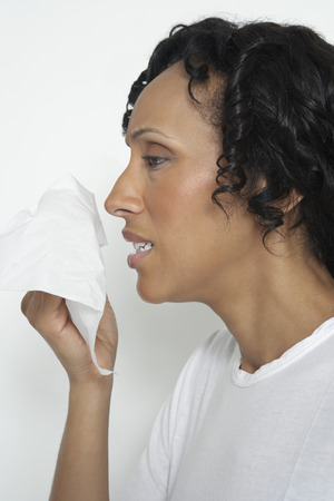 Woman holding tissue to face, studio shot Stock Photo - 3812921