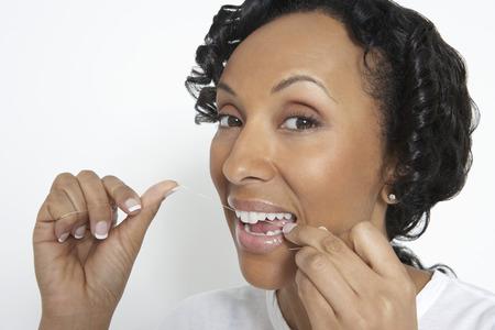 flossing: Woman flossing teeth, studio shot