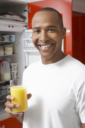 Man holding glass of orange juice, by fridge, portrait Stock Photo - 3812975