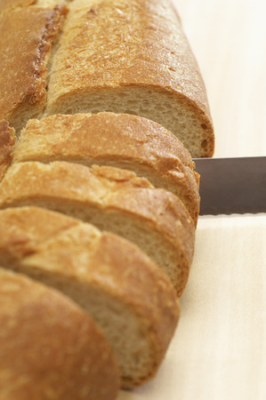 Close-up of knife slicing baguette Stock Photo - 3812981