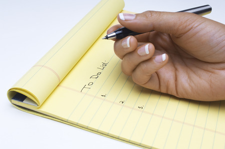 Woman writing list of tasks to do, close-up of hand Stock Photo