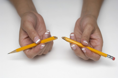 Woman holding broken pencil, close-up of hands Stock Photo - 3812801