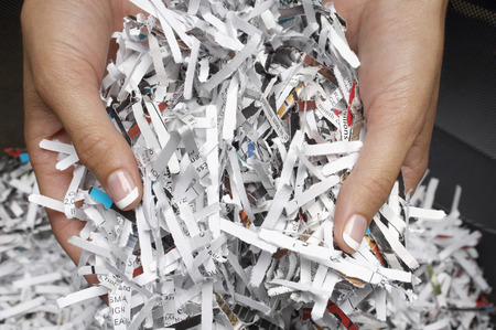 shredded paper: Woman holding heap of shredded paper, close-up of hands