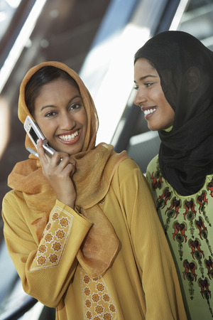Two muslim woman, one talking on mobile Stock Photo - 3906377