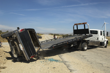 car lift: Man preparing to lift crashed car onto tow truck